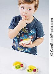 pequeno, menino, provando, a, bolo fruta