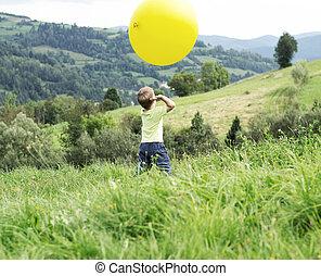 pequeno, menino, tocando, um, enorme, balloon