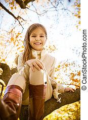 pequeno, sentando, tronco árvore, menina, feliz