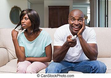 percé, séance femme, côté, elle, petit ami, regardant télé