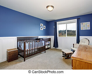 Perfect baby room with deep blue walls and nice crib.