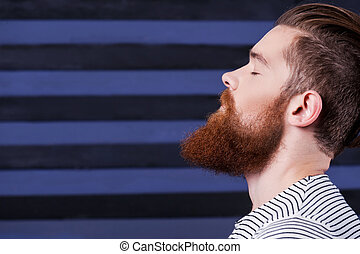 Perfect beard. Side view of handsome young bearded man holding hand on chin while standing against stripped background