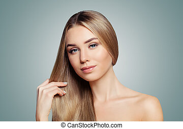 Perfect blonde woman showing her long healthy straight hair portrait. Hair care and hair straightening concept