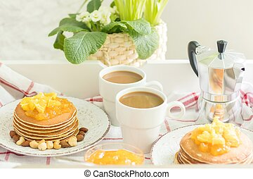 Perfect breakfast for 2. Tray with pancakes with orange jam and nuts on vintage plates and 2 white coffee cups