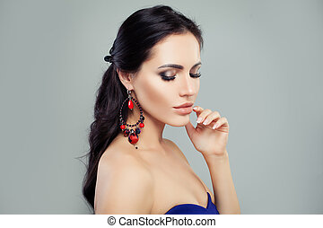 Perfect brunette woman with makeup and jewelry