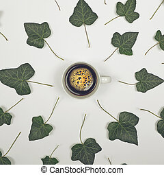 Perfect cup of coffee on white background with green leaves - Flat lay design