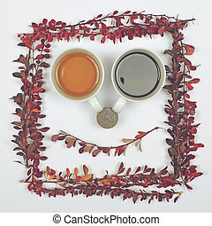 Perfect cup of tea and coffee on white background with autumn leaves in form of smiling face - Flat lay of Autumnal background