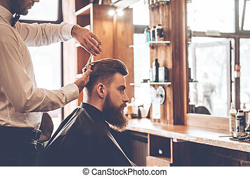 Perfect cut. Close-up side view of young bearded man getting haircut by hairdresser at barbershop