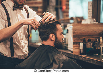 Perfect cut from back to front. Close-up of young bearded man getting haircut by hairdresser at barbershop