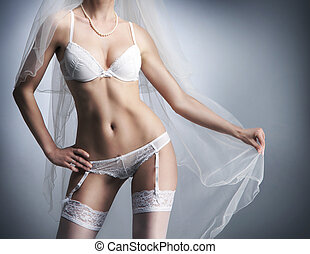 Perfect female body in sexy bridal lingerie over grey background