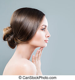 Perfect Female Face Closeup. Spa Woman with Healthy Skin touching her Hand her Face, Profile