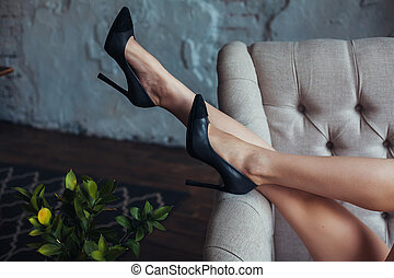 Perfect female legs in black shoes with high heels.