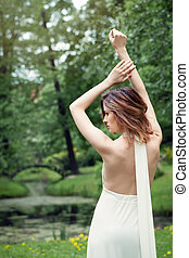 Perfect girl in white dress outdoor . Beautiful female back on green nature background