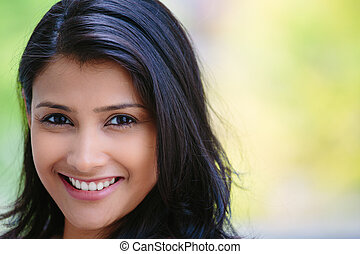 Closeup headshot portrait of confident smiling happy pretty young woman, isolated background of blurred trees. Positive human emotion facial expression feelings, attitude, perception