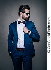 Perfect in his style. Handsome young man wearing sunglasses adjusting his jacket and looking over his shoulder while standing against grey background