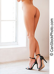 Perfect legs. Cropped rear view image of beautiful young naked woman in high heeled shoes standing in front of the window