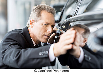 Perfect lines. Mature grey hair businessman examining car at...