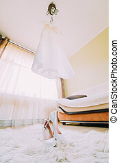 Perfect luxury wedding dress with a long train and skirt on hanger in room of the bride.