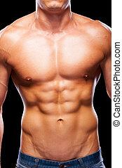 Perfect male torso. Close-up of young muscular man with perfect torso standing against black background