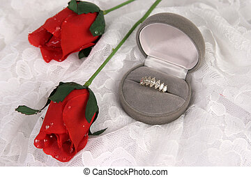 a diamond ring and silk roses over lace