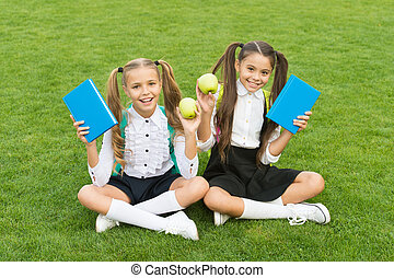 Perfect school children sit on grass with books, school time concept