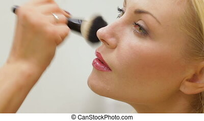 Beauty Girl with Makeup Brush. Makeover. Perfect Skin. Applying Makeup. Happy woman at the hair salon. Woman doing hairdress and a make-up.