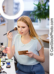 Pretty long haired woman applying facial powder