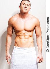 perfect, staand, zijn, baddoek, body., shirtless, jonge, tegen, grijze , het kijken, zeker, terwijl, fototoestel, achtergrond, bedekt, man