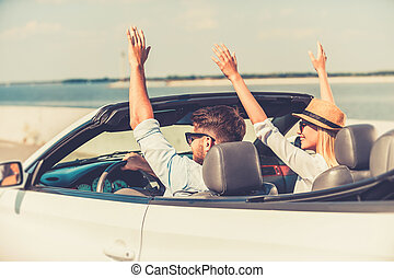 Perfect start of their weekend. Excited young couple keeping arms raised while riding in their white convertible