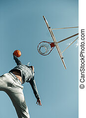 Low angle of a basketball player jumping