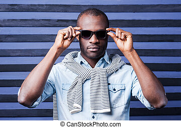 Perfect style. Handsome young African man adjusting his sunglasses while standing against striped background