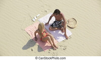 Young people having a perfect sunbath together lying on the white sand