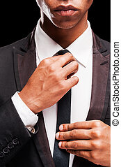 Perfect to the last detail. Fashionable young Afro-American man adjusting his necktie while standing against black background
