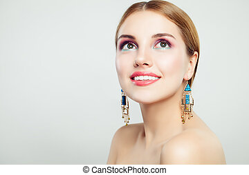Perfect young woman smiling and looking up, female beauty portrait. Makeup and gold earrings