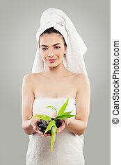 Perfect Young Woman with Green Bamboo Leaves and Massage Black Stones in her Hands. Massage, Bodycare and Spa Beauty Concept