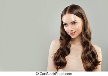 Perfect young woman with long healthy brown curly hairstyle portrait. Hair care concept