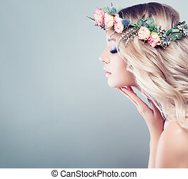 Perfect Young Woman with Spring Flowers. Blonde Beauty on Blue Background. Long Wavy Hair, Healthy Skin, Fashion Makeup