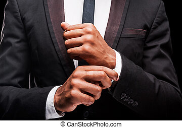 Perfection. Fashionable young Afro-American man adjusting his sleeves while standing against dark background