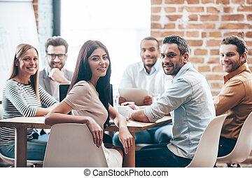 perfecto, team., grupo, de, seis, alegre, jóvenes, mirar cámara del juez, con, sonrisa, mientras, el sentarse en la tabla, en, oficina