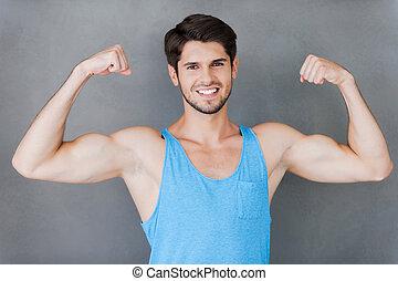 perfeitos, ficar, bíceps, seu, mostrando, jovem, muscular, cinzento, enquanto, contra, fundo, masculinity., homem, verdadeiro, bonito
