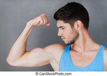 perfeitos, ficar, seu, mostrando, jovem, muscular, cinzento, confiante, enquanto, posar, contra, fundo, bicep., homem