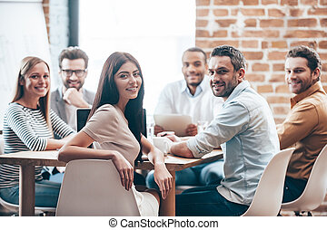 perfeitos, team., grupo, de, seis, alegre, jovens, olhando câmera, com, sorrizo, enquanto, sentar tabela, em, escritório