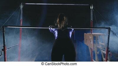 performance in gymnastics female gymnast in uneven bars. -...