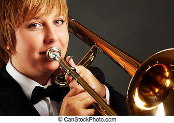 Performance - Portrait of young female playing the trombone...