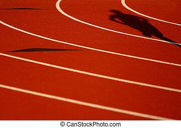 shadow of a runner on a red race track (focus is on the shadow and upper half of the picture)