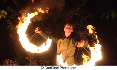 fire show, girl rotating flame on black trees background -...