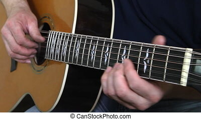 performer playing on the acoustic guitar.