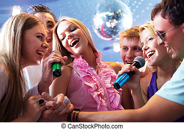 Portrait of joyous guys and girls singing at party together