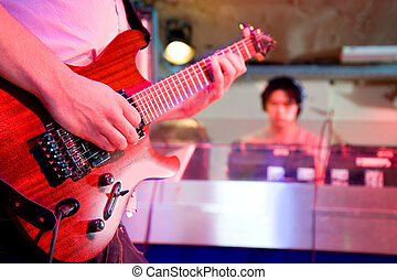 A live performance of a guitarist on stage playing together with a deejay. Viewed from the stage.