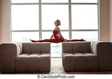 Elastic skinny girl doing yoga on furniture in living room -...
